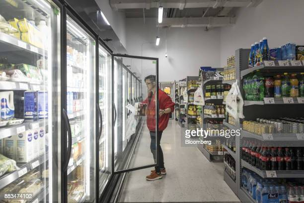 An employee looks inside a freezer while fulfilling an electronic order in a WalMart Stores Inc miniwarehouse for the company's onehour delivery...