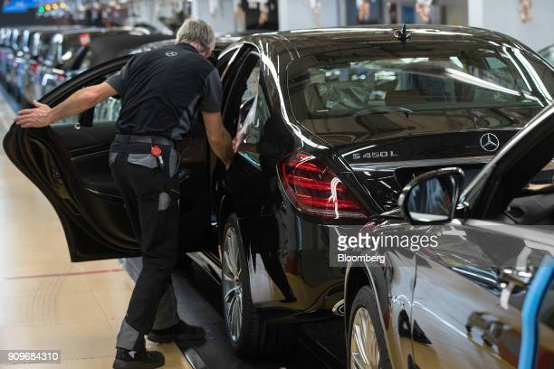 An employee looks inside a MercedesBenz SClass automobile as it stands on the final quality check line at the automaker's factory in Sindelfingen...