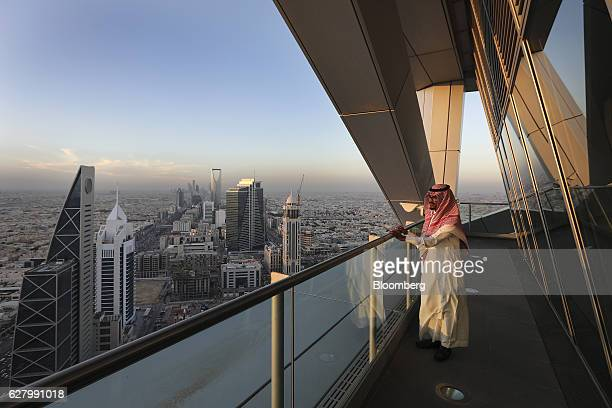 An employee looks out from the 32nd floor viewing platform of the Al Faisaliah Tower as skyscrapers and commercial buildings stand beyond in Riyadh...