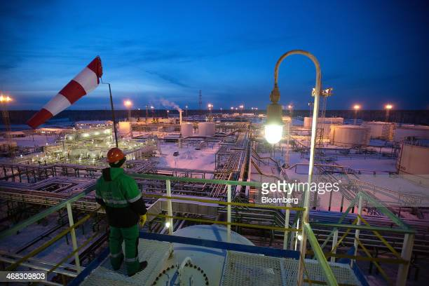 An employee looks out over the separator facility left illuminated at night in the central processing plant for oil and gas at the Salym Petroleum...