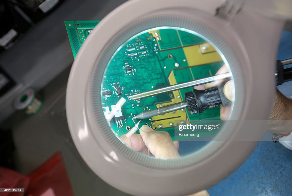 An employee looks through a magnifying glass as she solders a component onto a printed circuit board at Texcel Technology Plc's factory in Dartford, U.K., on Tuesday, July, 28, 2015. U.K. economic growth accelerated in the second quarter as business services and finance strengthened and North Sea output surged. Photographer: Chris Ratcliffe/Bloomberg via Getty Images