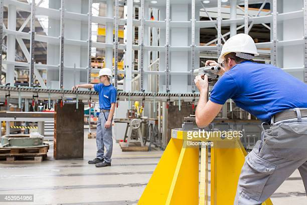 An employee looks through a Zeiss Ni2 Automatic Level optic manfactured by Carl Zeiss Meditec AG to measure the stator frame of a hydropower...