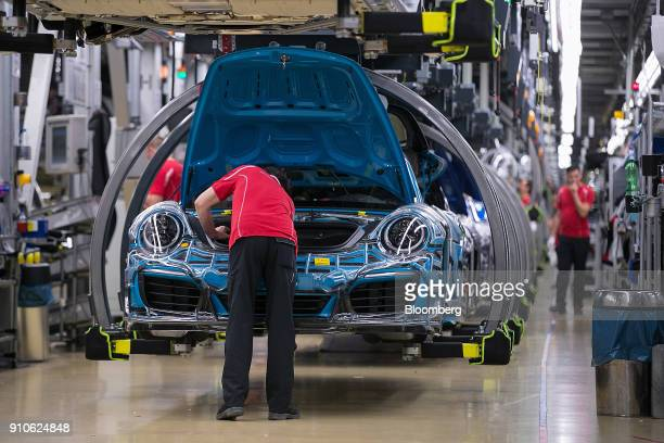 An employee looks under the hood of a Porsche 911 luxury automobile on the production line inside the Porsche AG factory in Stuttgart Germany on...