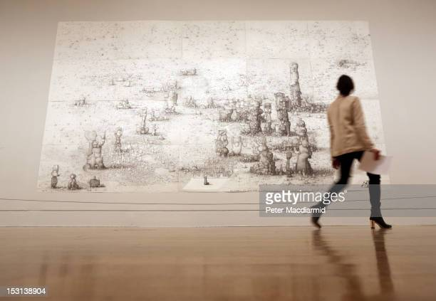 An employee looks up at Turner Prize nominee Paul Noble's 'Villa Joe 20056' on display at Tate Britain on October 1 2012 in London England The...