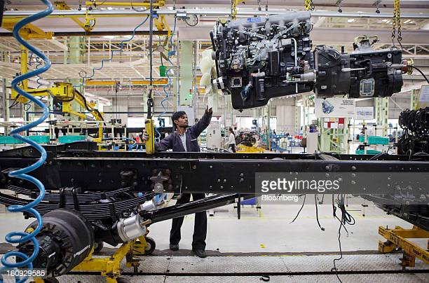 An employee lowers an engine onto a chassis on the assembly line for the Mahindra Mahindra Ltd Navistar truck at the company's factory in Chakan...