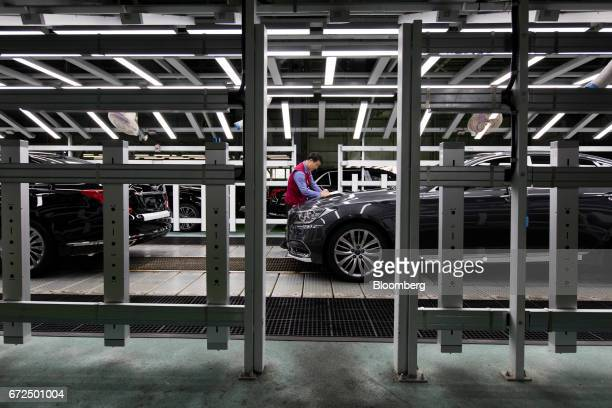 An employee make notes as he performs final inspections on a Hyundai Motor Co. Genesis luxury sedan on the production line at the company's plant in...