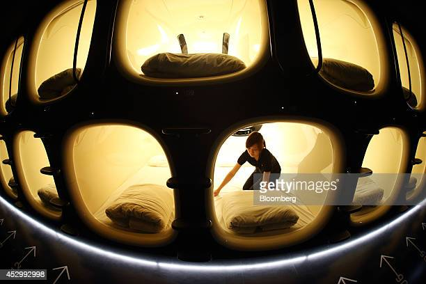 An employee makes a bed inside a capsule unit in the Nine Hours Narita Airport capsule hotel operated by nine hours Inc in this photograph taken with...