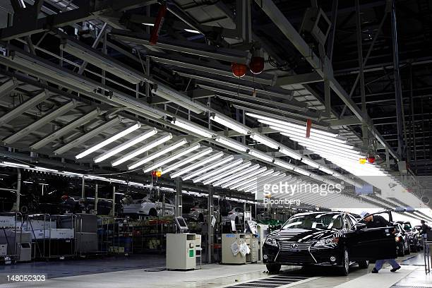 An employee makes a final inspection of a Toyota Motor Corp Lexus ES sedan on the production line of Toyota Motor Kyushu Inc's Miyata plant in...