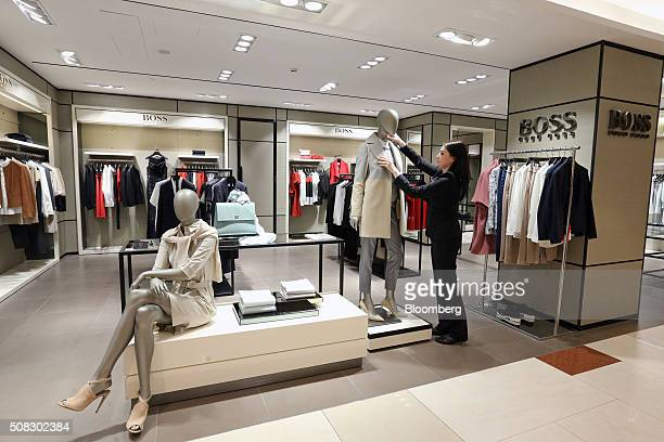 72143069 An employee makes adjustments to a mannequin display at the Hugo Boss AG  boutique inside the