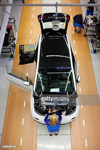 An employee makes adjustments under the hood of a new BMW i3 batterypowered vehicle manufactured by Bayerische Motoren Werke AG at the company's...