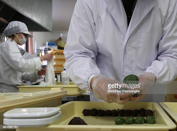 An employee makes Japanese sweet named Samuchi, which are made by Azuki bean and Mochi at Amaneya sweet shop on January 23, 2014 in Himeji, Japan....