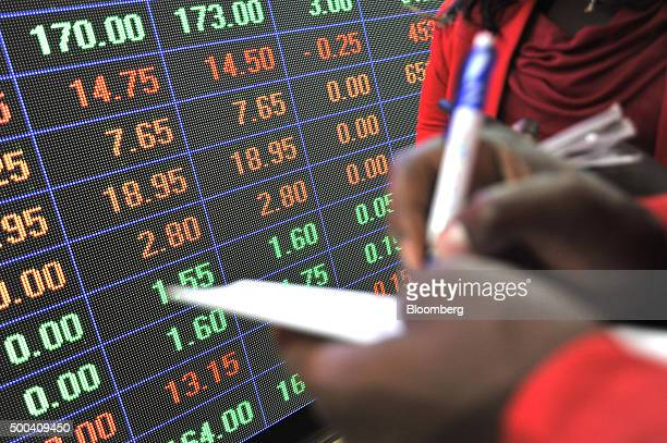 An employee makes notes in front of an electronic stock information screen inside the Nairobi Securities Exchange Ltd in Nairobi Kenya on Tuesday Dec...