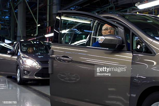 An employee makes quality control checks on a Ford Kuga SUV automobile at the Ford Espana SL plant operated by Ford Motor Co in Almusafes Spain on...