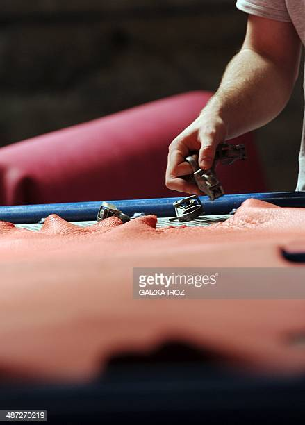 An employee manipulates skins to produce leather in the Remy Carriat tannery in Espelette southwestern France on April 10 2014 Since 1927 the tannery...