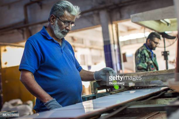 An employee marks a damaged tile moving along a conveyor at the Shabbir Tiles Ceramics Ltd production facility in Karachi Pakistan on Wednesday Dec 6...
