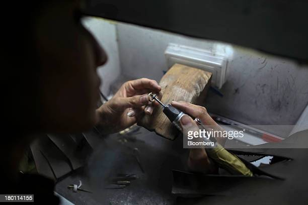An employee marks a gold ring for a possible correction inside the diamond studded gold and platinum manufacturing facility at Kama Schachter Jewelry...