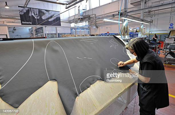 An employee marks a leather hide for use in the upholstery of a Lamborghini SpA automobile inside the company's factory in Sant'Agata Bolognese near...
