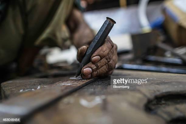 An employee marks a metal flat bar inside an Ishwar Engineering Co factory in Mumbai Maharashtra India on Saturday Feb 7 2015 The International...