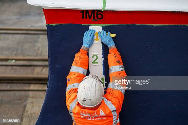 An employee marks the water depth reading on the stern of a Thames Clipper catamaran at Turks boatyard in Chatham UK on Thursday Oct 29 2015 The...