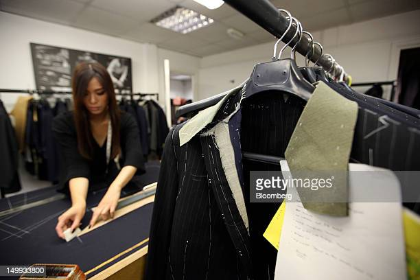 An employee marks up a piece of cloth with chalk in the workshop at the Gieves Hawkes store owned by Trinity Ltd on Saville Row in London UK on...