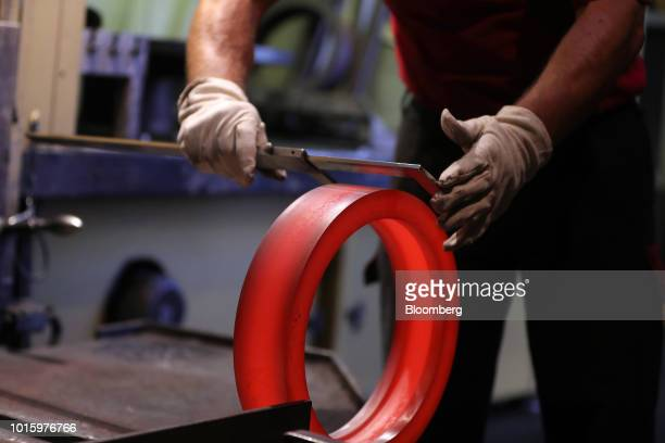 An employee measures a newly forged hot steel bearing component inside the Schaeffler AG factory in Schweinfurt Germany on Tuesday July 3 2018...