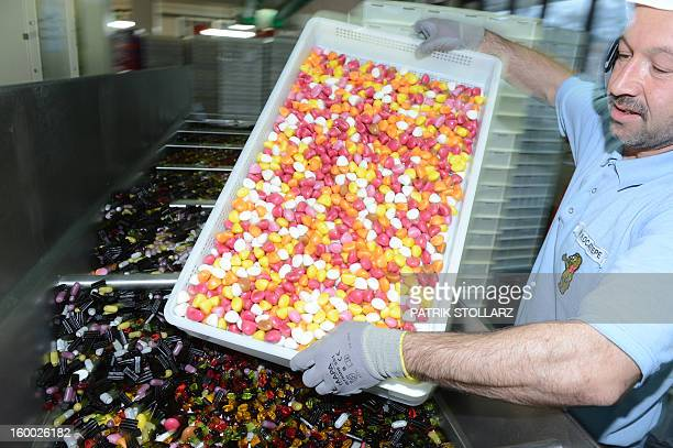 An employee mixes fruit gums after the production process at the HARIBO candy factory on January 24 2013 in Bonn western Germany AFP PHOTO / PATRIK...