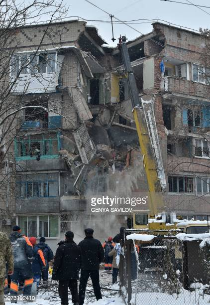 An employee monitoring a crane removes rubble from a partially destroyed fivestorey building on the site of a gas explosion in the town of Fastiv on...