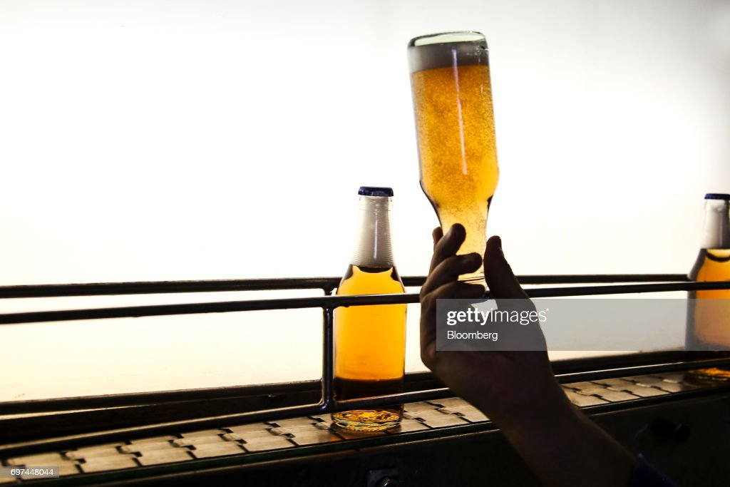 An employee monitors a bottle of nonalcoholic strawberry flavored malt moving along a conveyor at the Murree Brewery Co factory in Rawalpindi Punjab..