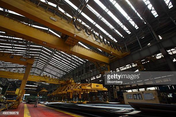 An employee monitors a gantry crane moving a sheet of steel at the Hyundai Mipo Dockyard Co shipyard an affiliate of Hyundai Heavy Industries Co in...