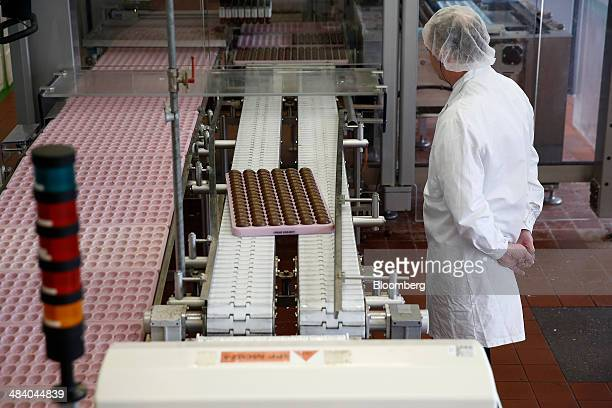 An employee monitors Cadbury Creme Eggs as they sit in a tray on the production line at the Bournville Cadbury factory operated by Mondelez...