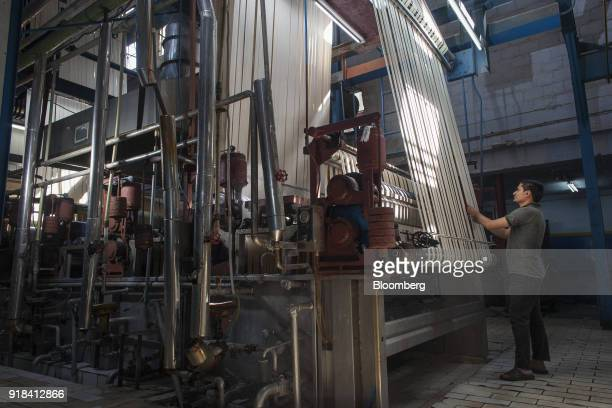 An employee monitors cotton rope moving through machinery in the dyeing plant at the Artistic Denim Mills Ltd factory in Karachi Pakistan on Tuesday...