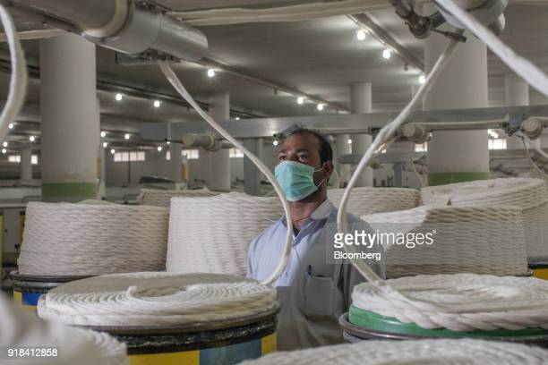 An employee monitors drawing machinery in the spinning unit at the Artistic Denim Mills Ltd factory in Karachi Pakistan on Tuesday Feb 6 2018...