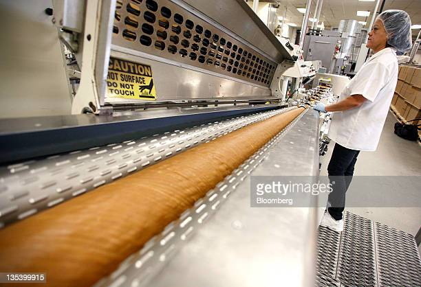 An employee monitors heated batch rollers containing butterscotch mix at the See's Candies Inc lollipop facility in Burlingame California US on...