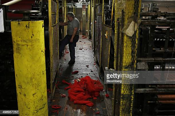 An employee monitors machinery used to refine red dyed wool at the Woolrich Inc woolen mill in Woolrich Pennsylvania US on Wednesday Nov 4 2015...