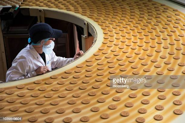 An employee monitors McVitie's Milk Chocolate Digestives biscuits on the production line at United Biscuits factory in London UK on Monday Sept 24...