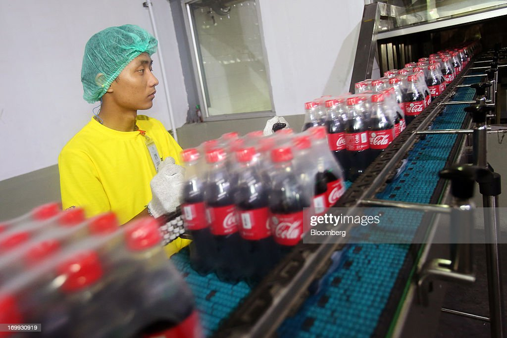 An employee monitors operations as packaged bottles of Coca-Cola soda move along the production line at the Coca-Cola Co. bottling plant in Hmawbi, Myanmar, on Tuesday, June 4, 2013. Coca-Cola Co. Chief Executive Officer Muhtar Kent marked the return of the world's largest soda maker to Myanmar after 60 years by opening a bottling plant and pledging more investment in the newly opened economy. Photographer: Dario Pignatelli/Bloomberg via Getty Images