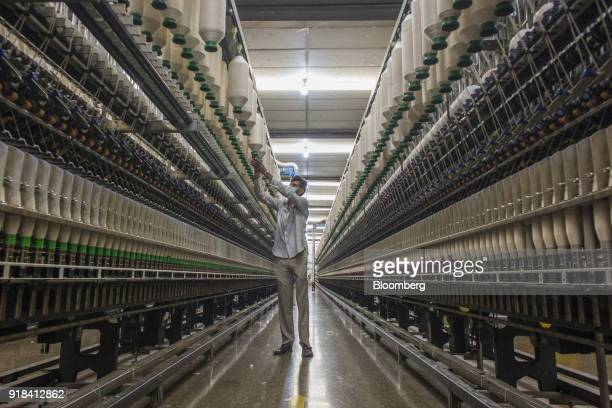 An employee monitors ring spinning machinery in the spinning unit at the Artistic Denim Mills Ltd factory in Karachi Pakistan on Tuesday Feb 6 2018...