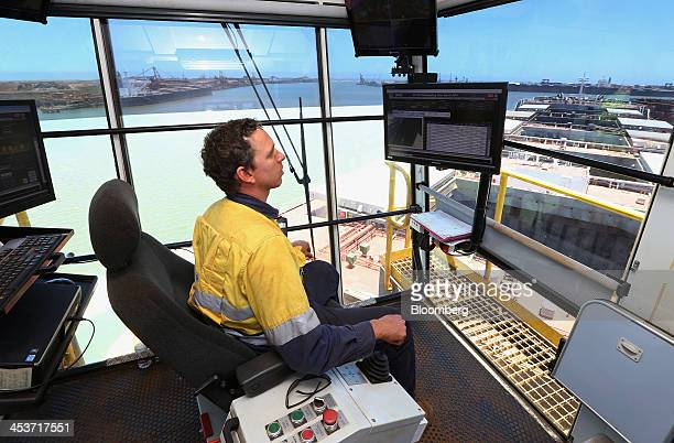 An employee monitors the flow of iron ore into a bulk carrier at the ship loading facility at Fortescue Metals Group Ltd's Herb Elliott Port in Port...