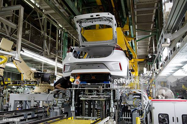 An employee monitors the installation of a battery pack into a Hyundai Motor Co. Ioniq electric vehicle on the production line at the company's plant...