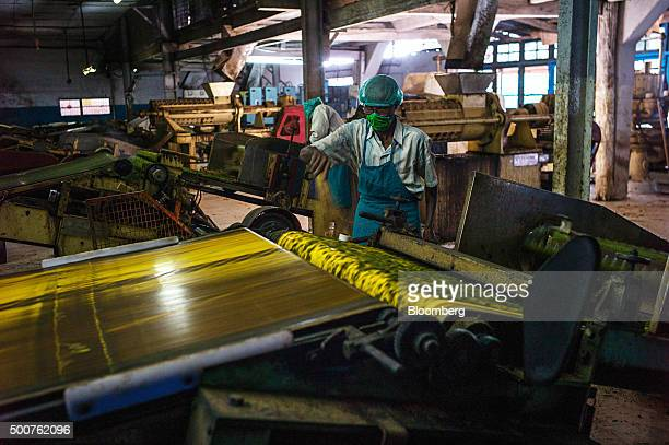 An employee monitors the operation of a tea leafrolling machine inside the factory at the Simulbari Tea Estate in Darjeeling district West Bengal...