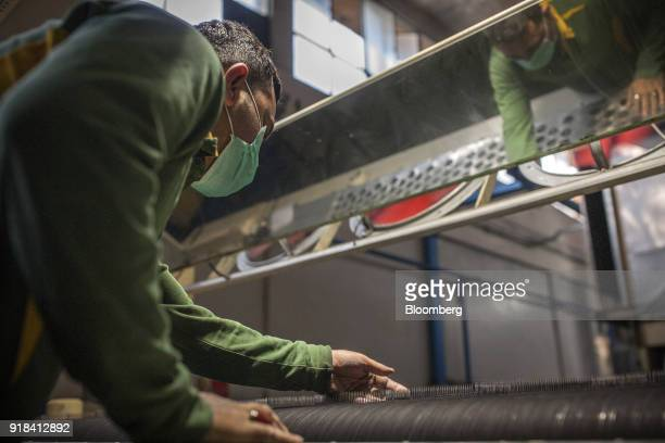 An employee monitors the tension of cotton threads on a loom in the weaving unit at the Artistic Denim Mills Ltd factory in Karachi Pakistan on...