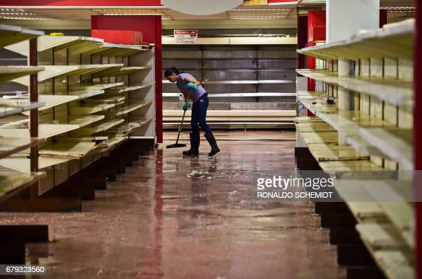 An employee mops at a supermarket in Valencia Carabobo State on May 5 the day after antigovernment protesters looted stores set fire to cars and...