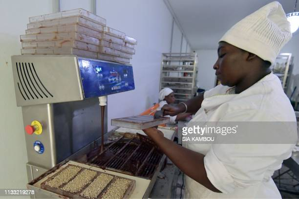 An employee moulds chocolate at the handmade organic raw chocolate factory Mon Choco in Abidjan on March 27 2019 Ivorian Dana Mroueh of...