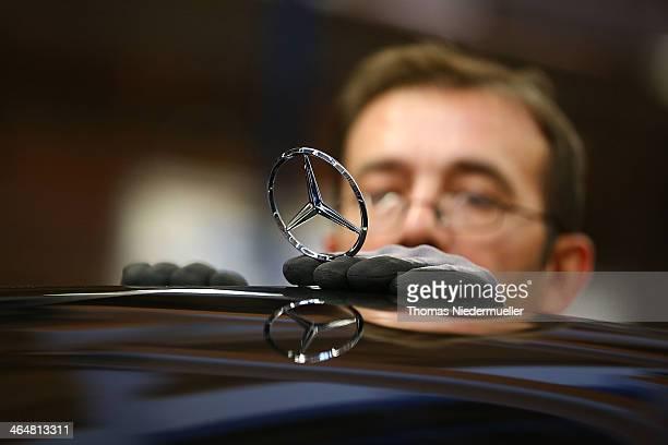 An employee mounts a Daimler AG MercedesBenz emblem to the hood of a SClass sedans on the assembly line at the MercedesBenz plant of Daimler AG on...