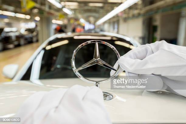 An employee mounts a Daimler AG MercedesBenz emblem to the hood of a SClass sedans at the MercedesBenz plant on January 24 2018 in Sindelfingen...