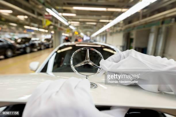 An employee mounts a Daimler AG MercedesBenz emblem to the hood of a SClass sedans at the MercedesBenz plant on January 24 2018 in Sindelfingen...