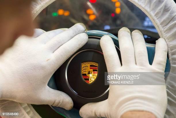 An employee mounts a steering wheel in a Porsche sportscar on the assembly line in the factory of German luxury car producer Porsche in Stuttgart...