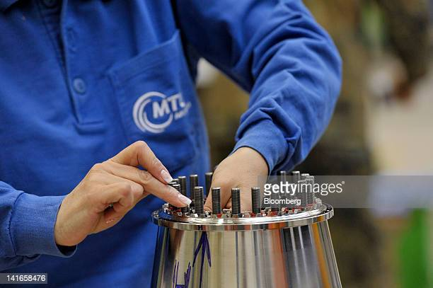 An employee mounts parts on the high pressure compressor of an EJ200 engine manufactured by MTU Aero Engines Holding AG for use on an Eurofighter...