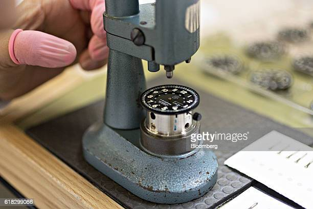 An employee mounts the dial of a Luminox P38 lightening automatic 9401 series wristwatch onto a hand press at the Mondaine Watch Ltd production...