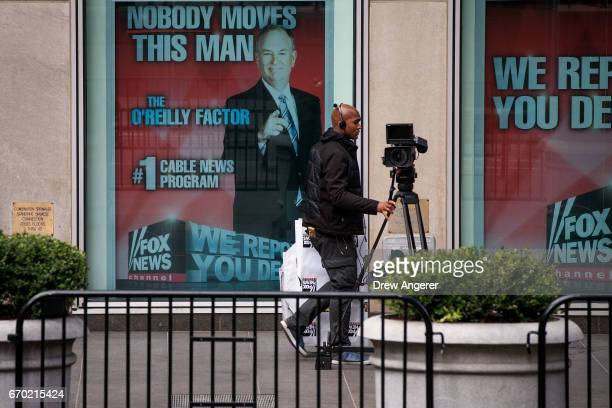 An employee moves a camera past an advertisement for Bill O'Reilly outside of the News Corp and Fox News headquarters in Midtown Manhattan April 19...